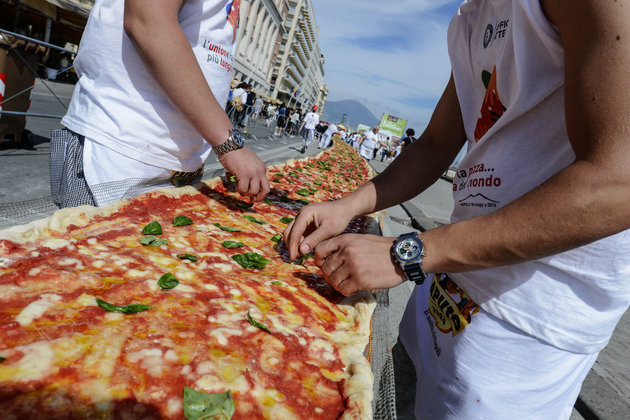 Neapolitan pizza makers attempt to make the longest pizza to break a Guinness World Record along the seafront of Naples, on May 18, 2016. For the wood-fired pizza, which measured two kilometres, they used 2,000 kg of flour, 1,600 kg of tomatoes, 2,000 kg of mozzarella, 200 litres of oil, 30kg of fresh basil. The record-breaking snack measured up at exactly 1,853.88 metres (6,082 feet), smashing the previous record of 1,595.45 metres (5,234 feet) set at last year's World Expo in Milan, Italy's food and agriculture board Coldiretti said. / AFP / Mario LAPORTA        (Photo credit should read MARIO LAPORTA/AFP/Getty Images)