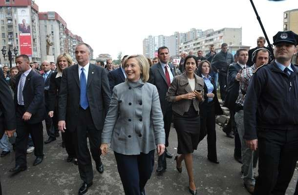 US Secretary of State Hillary Clinton (C) smiles as she walks to of a store named in her honour, which is located next to an unseen statue of her husband, former US president Bill Clinton, on a stop driving from the airport to Pristina October 13, 2010. Kosovo prepared a warm welcome for US Secretary of State Hillary Clinton where she is expected to push for EU brokered talks between Belgrade and Pristina to start as soon as possible. AFP PHOTO / Mandel NGAN (Photo credit should read MANDEL NGAN/AFP/Getty Images)