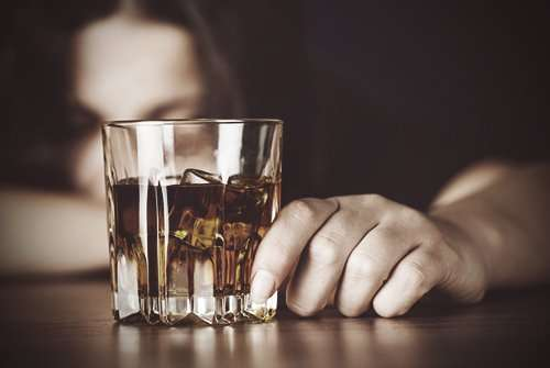 drugabuse-shutterstock293848514-woman_in_front_of_alcohol_glass-feature_image-alcohol_abuse